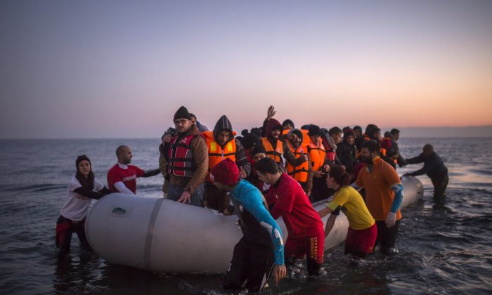 Volunteers help refugees and migrants who are approaching the Greek island of Lesbos on a dinghy after crossing the Aegean sea from the Turkey's coast on Dec. 7, 2015. (AP Photo/Santi Palacios)