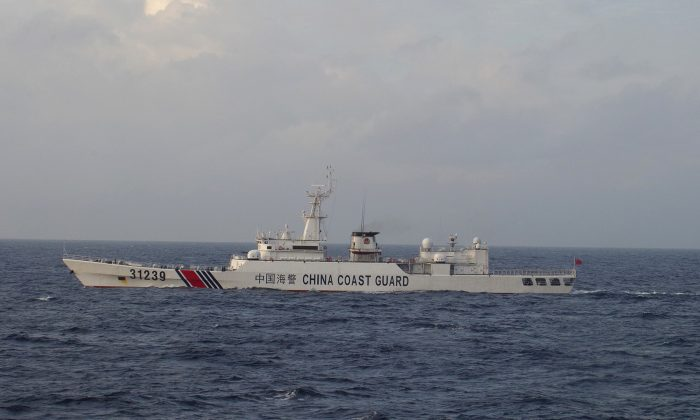 In this photo provided by Japan Coast Guard, an armed Chinese coast guard ship sails in the water near islands, known as the Senkaku in Japanese and the Diaoyu in Chinese, Tuesday, Dec. 22, 2015. (Japan Coast Guard via AP)