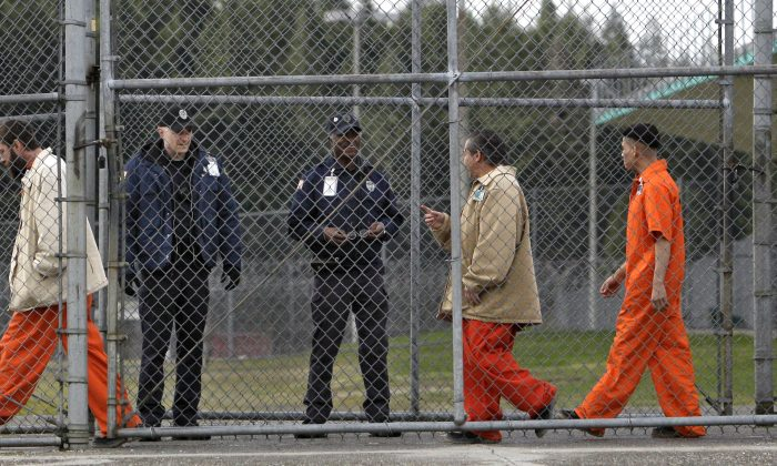 Inmates walk past correctional officers at the Washington Corrections Center in Shelton, Wash., on Feb. 17, 2011. Gov. Jay Inslee said Tuesday, Dec. 22, 2015 that more than 3,000 prisoners in Washington have been mistakenly released early since 2002 because of an error by the state's Department of Corrections. (AP Photo/Elaine Thompson)