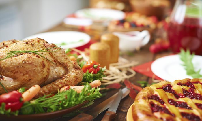 Roasted meat with garnish and cowberry pie on festive table. (shironosov/iStock)