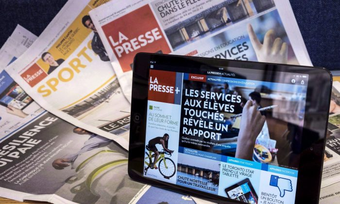 A tablet is seen on the newspaper edition of a La Presse newspaper. Advertisers are packing up their campaigns and moving out of print media at a pace that shows no sign of slowing over the next four years, according to a new report. (The Canadian Press/Paul Chiasson)