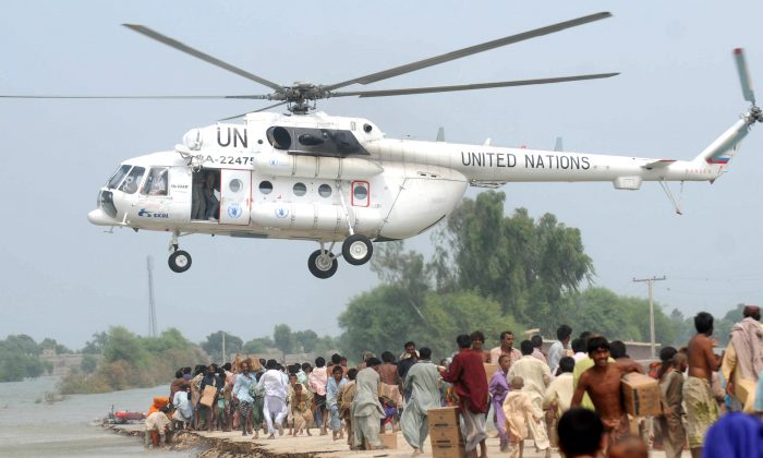 An U.N. helicopter drops relief goods to Pakistanis displaced by floods on higher ground in the flood-hit Chandan Village, Dadu District, on Sept. 10, 2010. (Rizwan Tabassum/AFP/Getty Images)