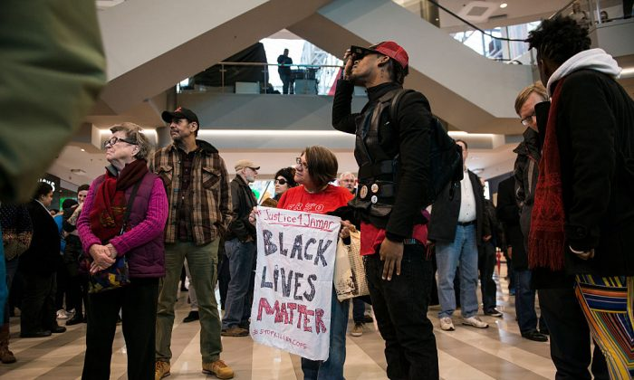 Activist, Jess Sundin, holds a sign that reads, 'BLACK LIVES MATTER,' in the rotunda of the Mall of America on December 23, 2015 in Bloomington, Minnesota. To Sundin's right stands Alexander Clark, cousin of Jamar Clark who was shot and killed by Minneapolis Police in November. Black Lives Matter Minneapolis staged a brief protest at the Mall of America in Bloomington, MN before moving their protest to the airport. (Photo by Stephen Maturen/Getty Images)