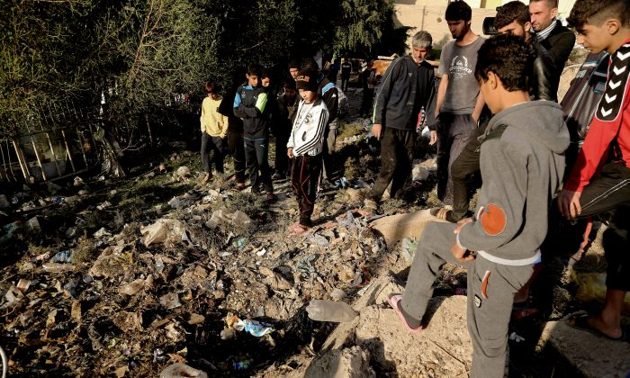 Civilians inspect the aftermath of a suicide bomb attack on Al- Rahman Shiite Mosque in Baghdad's al-Ubeidi  neighborhood, Iraq, Wednesday, Dec. 9, 2015. (AP Photo/Karim Kadim)