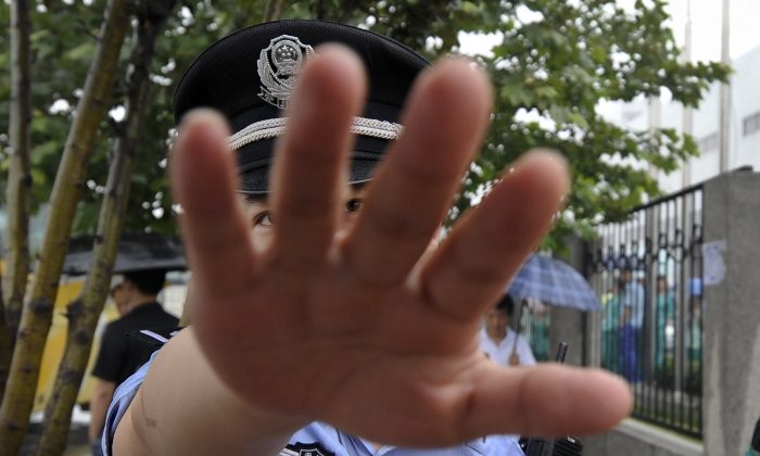 A Chinese police officer tries to block the photographer from taking pictures in Tianjin, China, on July 1, 2010. (AP Photo/Andy Wong)