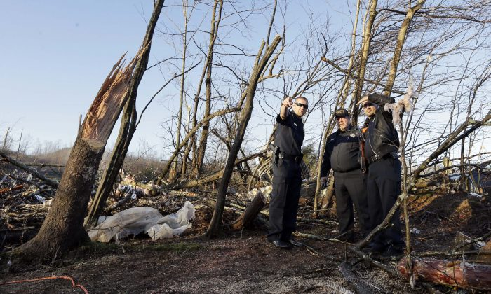 Members of the Perry County Sheriff's Department look over the site where Antonio Yzaguirre, 70, and his wife, Ann Yzaguirre, 69, were found dead, near Linden, Tenn., Thursday, Dec. 24, 2015. (AP Photo/Mark Humphrey)