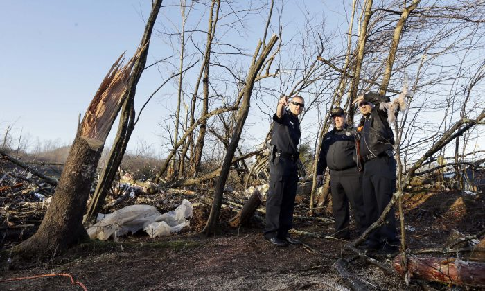 Members of the Perry County Sheriff's Department look over the site where Antonio Yzaguirre, 70, and his wife, Ann Yzaguirre, 69, were found dead, near Linden, Tenn., Thursday, Dec. 24, 2015. Several people were killed in Mississippi, Tennessee and Arkansas as spring-like storms mixed with unseasonably warm weather spawned rare Christmastime tornadoes in the South. (AP Photo/Mark Humphrey)