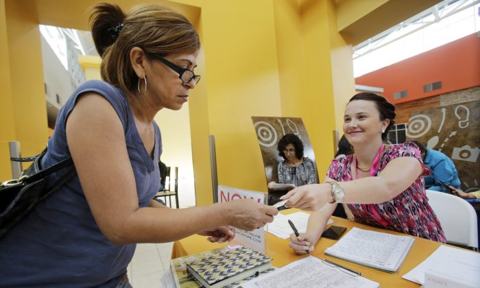 In this Tuesday, Oct. 6, 2015, photo, A'GACI clothing store hiring manager Marcie Lowe, right, gives her card to job applicant Xionara Garcia, left, of Miami, during a job fair at Dolphin Mall in Miami. (AP Photo/Wilfredo Lee)