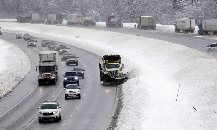A snowplow makes its way along an eastbound lane of Interstate 90 as trucks on the westbound lane behind are parked while drivers remove chains Tuesday, Dec. 22, 2015, at Snoqualmie Pass, Wash. .(AP Photo/Elaine Thompson)