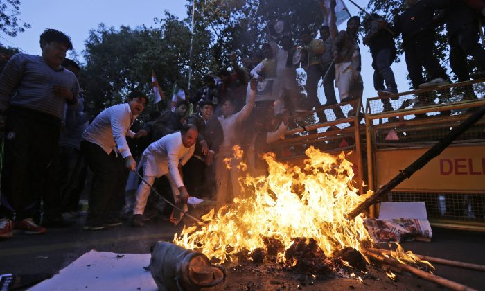 Members of the Indian Youth Congress burn an effigy of Indian Prime Minister Narendra Modi to protest against his visit to Pakistan in New Delhi, India, Friday, Dec. 25, 2015. Modi arrived in Pakistan on Friday, his first visit as prime minister to the Islamic nation that has been India's long-standing arch rival in the region. (AP Photo/Altaf Qadri)
