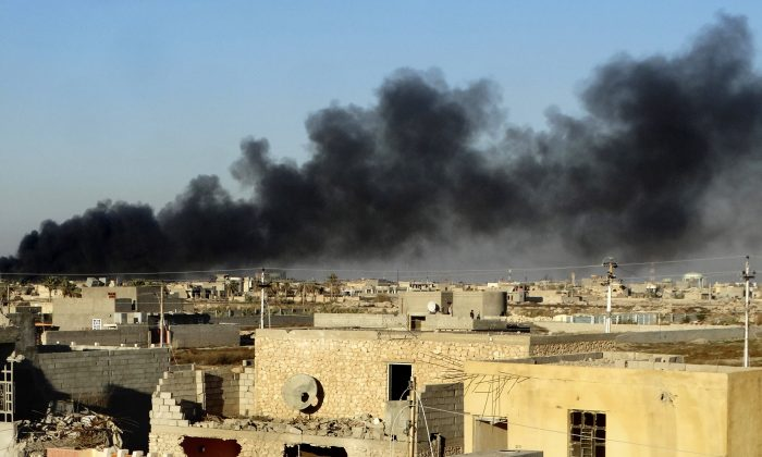 In this Friday, Dec. 25, 2015 photo, smoke rises from Islamic State positions following a U.S.-led coalition airstrike as Iraqi Security forces advance their position in downtown Ramadi, 70 miles (115 kilometers) west of Baghdad, Iraq. Iraqi forces entered the Huz at dawn, an area housing a government compound in the center of Ramadi, part of a major offensive aimed at dislodging the Islamic State terrorist militia from the western city, an Iraqi official said. (AP Photo)