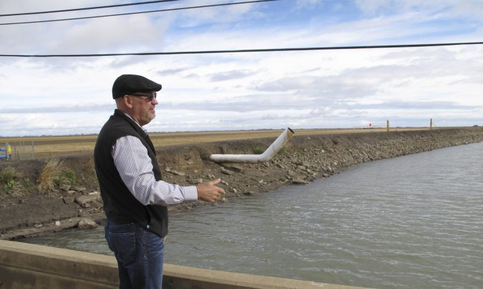 Chris White, general manager of the Central California Irrigation District, explains the expense of sinking land near Dos Palos, Calif., on Dec. 22, 2015. (AP Photo/Scott Smith)