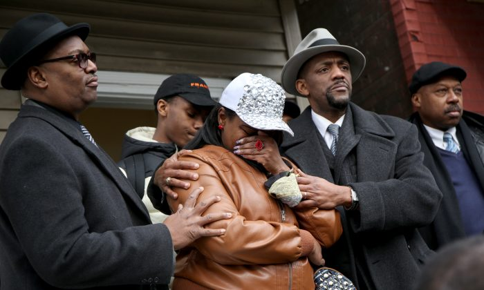 LaTarsha Jones, center, the daughter of Bettie Jones, is comforted by family and friends during a news conference on Sunday, Dec. 27, 2015, in front of the house where Bettie Jones was killed Saturday in the West Garfield Park neighborhood of Chicago.  (Nancy Stone/Chicago Tribune via AP)