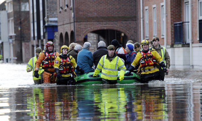 Members of the army and rescue teams help evacuate people from flooded properties after they became trapped by rising floodwater when the River Ouse bursts its banks in York city center Sunday, Dec. 27, 2015. (John Giles/PA via AP)