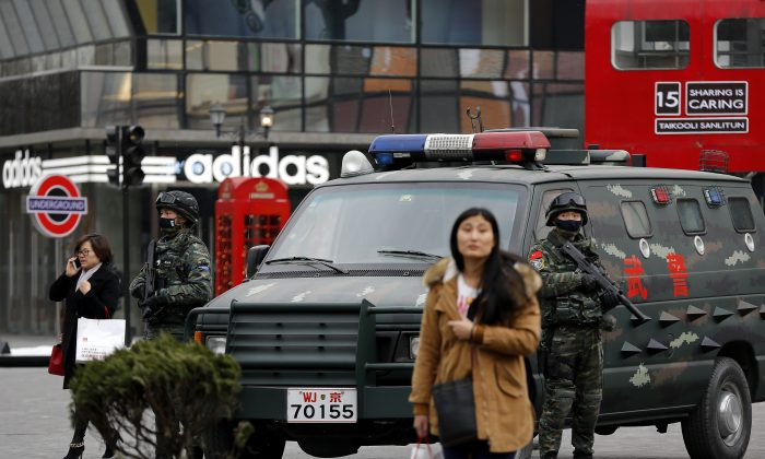 Armed Chinese paramilitary policemen stand guard in the capital city's popular shopping and nightlife area of Sanlitun in Beijing on Dec. 27, 2015.  (AP Photo/Andy Wong)