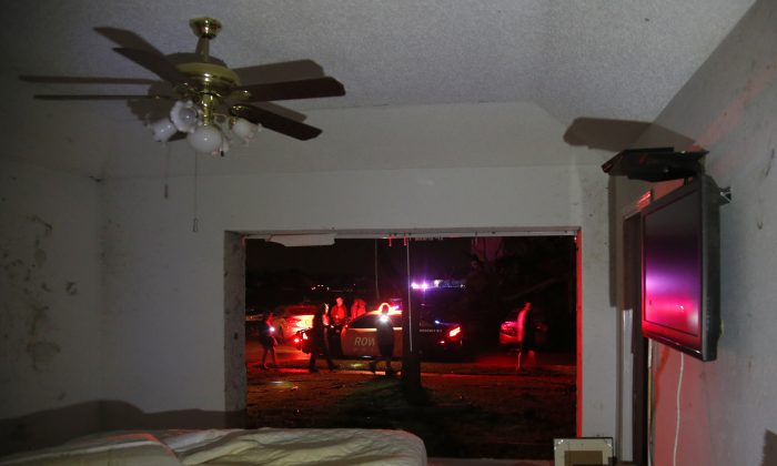 Rowlett first responders work in the street across from Daniel O'Connor's heavily damaged home after reports of a tornado in Rowlett, Texas, Saturday, Dec. 26, 2015. The large window in O'Connor's bedroom was completely ripped out and debris blown in. O'Connor was in another room when the tornado struck and was uninjured. (Guy Reynolds/The Dallas Morning News via AP) MANDATORY CREDIT; MAGS OUT; TV OUT; INTERNET USE BY AP MEMBERS ONLY; NO SALES