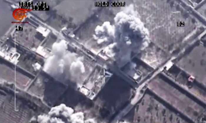 This image made from video made available on Saturday, Dec. 26, 2015, by Al-Mayadeen, government-controlled Syrian Television, which has been verified and is consistent with other AP reporting shows, drone footage allegedly showing Syrian army airstrikes targeting Zahran Allouch, the head of the Army of Islam group near Damascus, Syria. Militant groups in Syria on Saturday mourned the death of a powerful rebel commander who was killed in an airstrike near Damascus — a high profile assassination that may shift the balance of power in rebel-held suburbs of the Syrian capital. Allouch, was killed Friday, Dec. 25 in an airstrike that targeted the group's headquarters during a meeting.  (Al-Mayadeen via AP video)