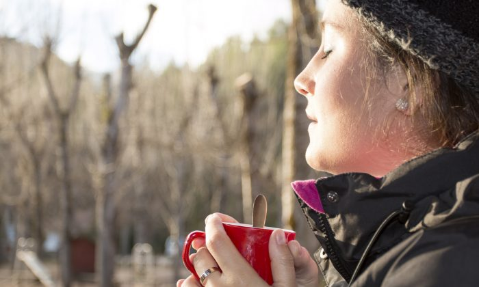 Beautiful woman holding a red mug with coffee at the sunrise