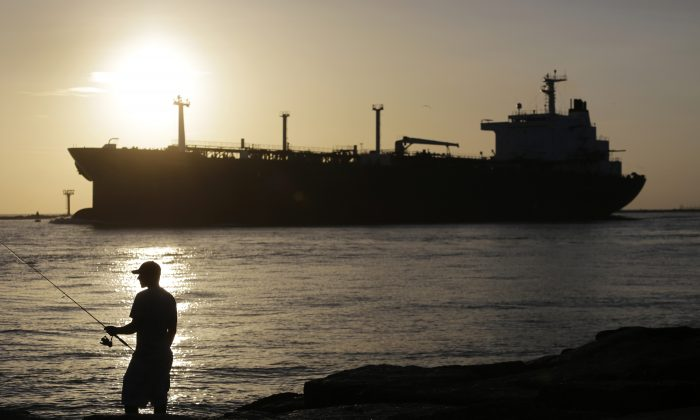 FILE - In this July 21, 2015, file photo, an oil tanker passes a fisherman as it enters a channel near Port Aransas, Texas, heading for the Port of Corpus Christi. The U.S., seemingly awash in crude oil after an energy boom sent thousands of workers scurrying to the plains of Texas and North Dakota, will begin exporting oil for the first time since the 1973 oil embargo.  (AP Photo/Eric Gay, File)