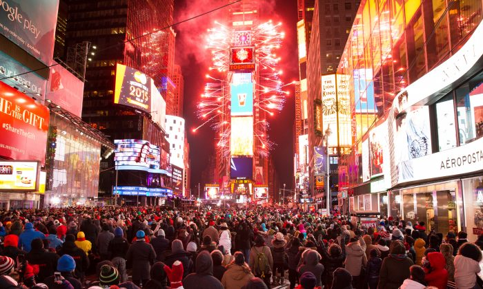 People cheer as the ball drops at midnight in Times Square, New York City, on Jan. 1, 2015. An estimated one million people from around the world are expected to pack Times Square to ring in 2015. (Dai Bing/Epoch Times)