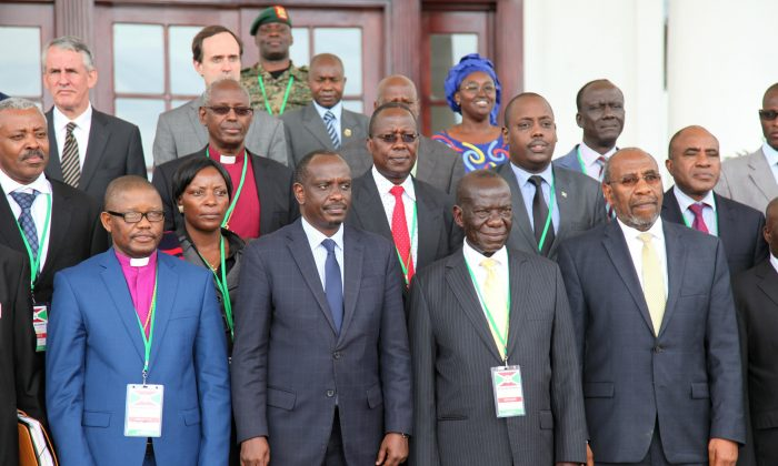 Uganda Vice President Edward Sekandi (2L), Uganda Prime Minister Dr. Ruhakana Rugunda (R), and East African Community Secretary-General Dr. Sezibwera (2R) pose with others, during Burundi peace talks at Entebbe State House, about 42 kilometers east of Uganda capital Kampala, on Dec. 28, 2015. Representatives of Burundi's government and the opposition are in Uganda for negotiations aimed at ending political violence. Burundian President Pierre Nkurunziza, whose decision to run for election to a third term triggered the bloodshed, wasn't present at the opening ceremony Monday. (AP Photo/Stephen Wandera)