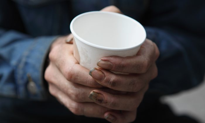 A homeless man holds a cup as he begs panhandles for spare change in San Francisco, Calif., on Sept. 16, 2010. (Justin Sullivan/Getty Images)