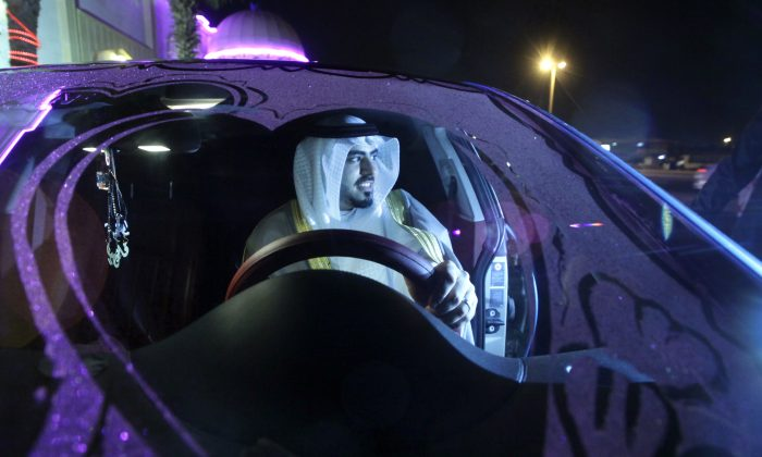 Saudi groom Hisham Saleh Edris drives his decorated car as he arrives alone at the men's section of the wedding hall in Jiddah, Saudi Arabia, on Sept. 8, 2015. (AP Photo/Amr Nabil)