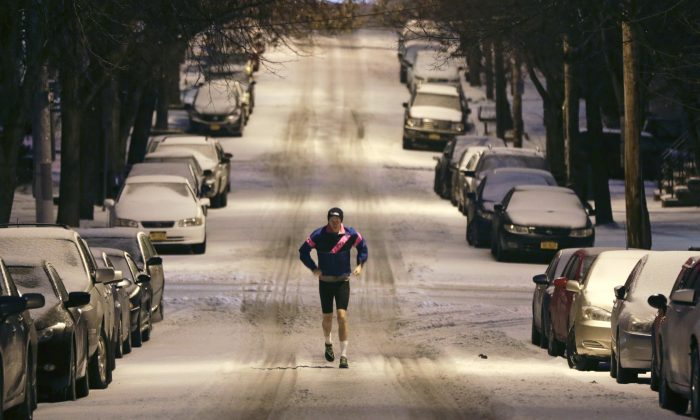 A jogger makes his way along a snow-covered street in the Hudson Park neighborhood, Tuesday, Dec. 29, 2015, in Albany, N.Y. Snow, sleet, freezing rain and gusty winds are creating treacherous driving conditions across upstate New York as eastern parts of the state receive their first severe weather of the winter season. (AP Photo/Mike Groll)