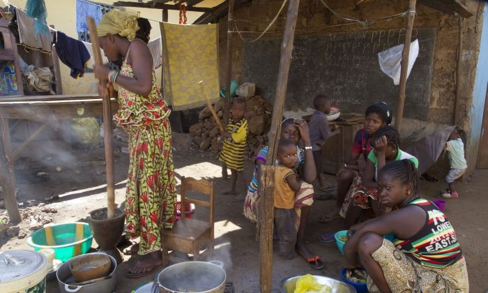 People prepare food at a homestead in Conakry City, Guinea, on Dec. 29, 2015. (AP Photo/Youssouf Bah)