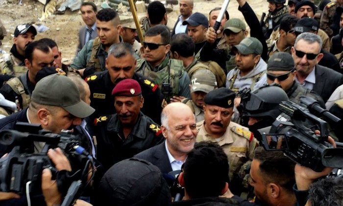 Iraqi Prime Minister Haider al-Abadi, center, smiles as he tours the city of Ramadi after it was retaken by the security forces in Ramadi, 70 miles (115 kilometers) west of Baghdad, Iraq, Tuesday, Dec. 29, 2015. (AP Photo)