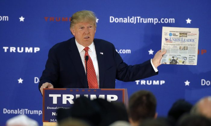 Republican presidential candidate Donald Trump displays a copy of the Union Leader newspaper while addressing an audience during a campaign event Monday, Dec. 28, 2015, in Nashua, N.H. (AP Photo/Steven Senne)