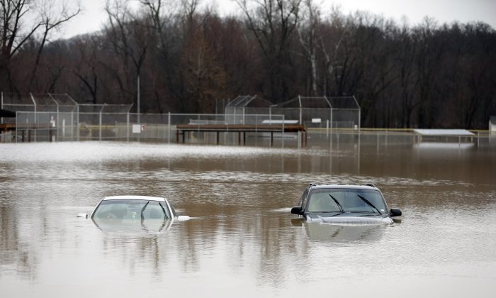Two cars are submerged in floodwater in a park Monday, Dec. 28, 2015, in Kimmswick, Mo. Missouri Gov. Jay Nixon has declared a state of emergency due to wide spread flooding around the state that has closed many roads. (AP Photo/Jeff Roberson)