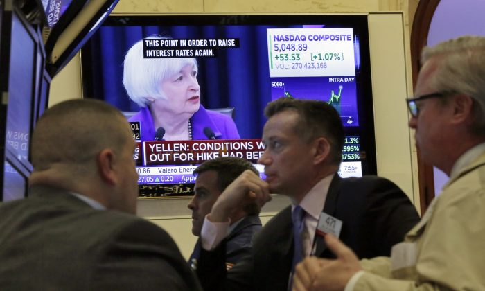 Federal Reserve Chair Janet Yellen's Washington news conference is shown on a television screen on the floor of the New York Stock Exchange on Dec. 16, 2015. Wall Street watched few things more closely this year than the Fed. Despite veering between record highs and the steepest dive in four years, the stock market is on track to end the year essentially flat. (AP Photo/Richard Drew)