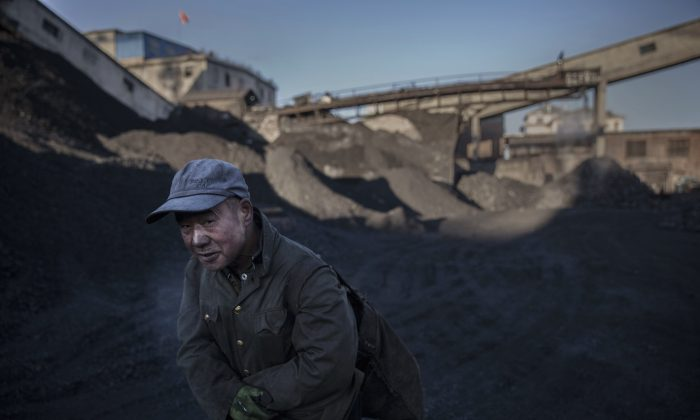 A Chinese man carries coal he collected from a sorting area at a coal mine on November 25, 2015 in Shanxi, China. (Kevin Frayer/Getty Images)