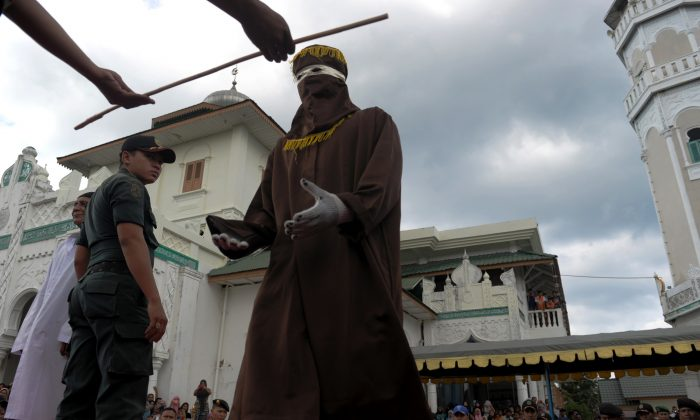 A member of the sharia police receives a cane as officials conduct punishment based on Islamic sharia law in Banda Aceh on December 28, 2015.  Aceh is the only province of Indonesia enforcing the Islamic Sharia law and offenders are punished by public caning. (Chaideer Mahyuddin/AFP/Getty Images)