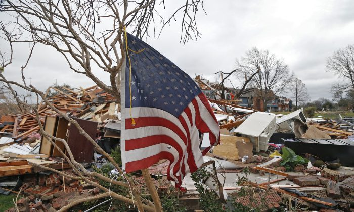 A tattered U.S. flag that had been attatched to a tree waves over the debris at the Landmark at Lake Village North Apartments as the recovery process begins following tornadoes which hit the area late Saturday night December 28, 2015 in Garland, Texas. (Stewart F. House/Getty Images)