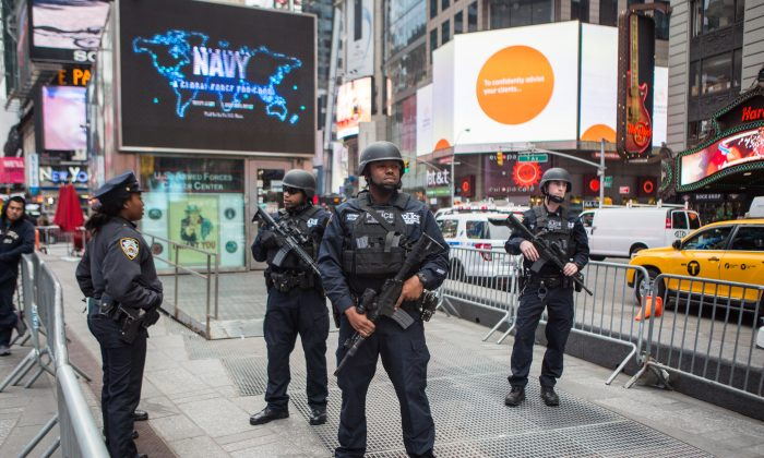 Members of the NYPD Strategic Response Group and an NYPD officer stand guard in New York's Times Square on Nov. 18, 2015. (Benjamin Chasteen/Epoch Times)
