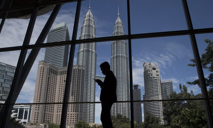 A worker is silhouetted against Malaysia's Petronas Twin Towers ahead of the ASEAN Summit at the Kuala Lumpur Convention Center in Kuala Lumpur on Nov. 17, 2015. (AP Photo/Vincent Thian)