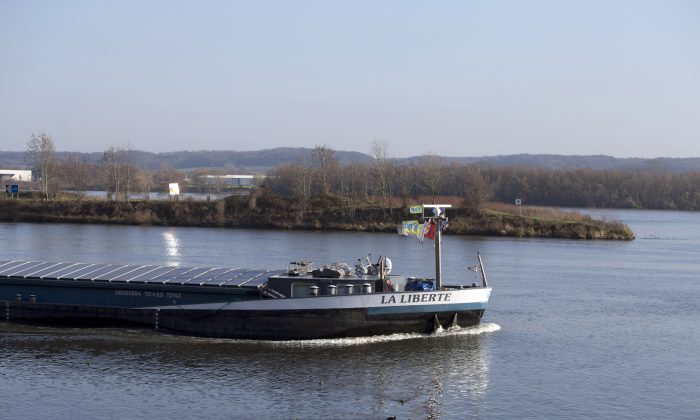 Dutch flagged ship passes by a Dutch owned island as it moves from Dutch owned waters into Belgian owned waters near Sint-Pietersberg, Netherlands, on Dec. 14, 2015. (AP Photo/Virginia Mayo)