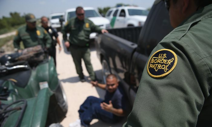 U.S. Border Patrol agents detain a suspected smuggler after he allegedly transported undocumented immigrants who crossed the Rio Grande from Mexico into the United States in Mission, Texas, on July 24, 2014. (John Moore/Getty Images)