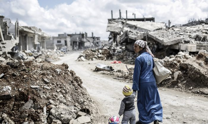 A Kurdish Syrian woman walks with her child past the ruins of the town of Kobani, also known as Ain al-Arab, on March 25, 2015. (Yasin Akgul/AFP/Getty Images)