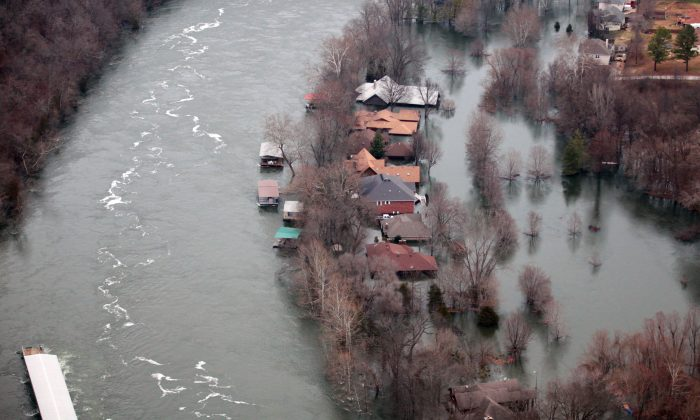 Floodwaters from Lake Taneycomo surrounded several homes in a neighborhood in Branson, Mo., after a record amount of water was released from the Table Rock Lake Dam, on Dec. 29, 2015. (Nathan Papes/The Springfield News-Leader via AP)