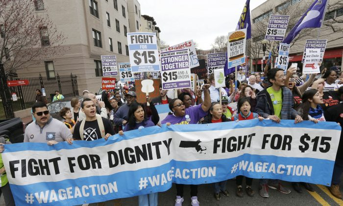Protesters, including college students, fast-food restaurant employees and other workers, display placards and chant slogans as they march in Boston, April 14, 2015. (AP Photo/Steven Senne, File)