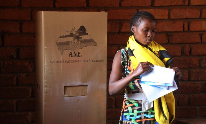 A woman folds her ballots before casting her vote during elections in Bangui, Central African Republic, Wednesday, Dec. 30, 2015. Thousands in Central African Republic's capital voted Wednesday in national elections with hope that a new president will lead to greater stability after years of violence. (AP Photo/Herve Serefio Diaspora)