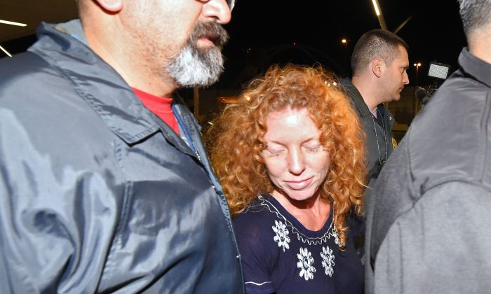 """Tonya Couch, center, is taken by authorities to a waiting car after arriving at Los Angeles International Airport, Thursday, Dec. 31, 2015, in Los Angeles. Authorities said she and her son, Texas teenager Ethan Couch, who was sentenced to probation after using an """"affluenza"""" defense for a 2013 wreck in Texas, fled to Mexico together in November as prosecutors investigated whether he had violated his probation. Both were taken into custody Monday, Dec. 28, after authorities said a phone call for pizza led to their capture in the resort city of Puerto Vallarta. (AP Photo/Mark J. Terrill)"""