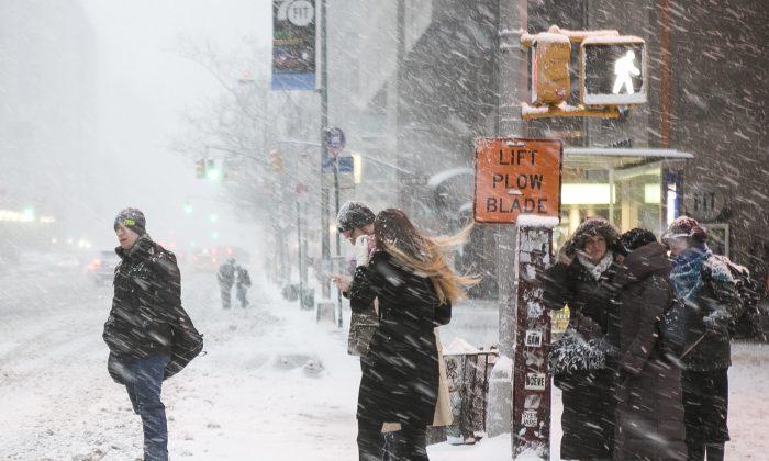 People cross a street during a blizzard in Midtown Manhattan on Jan. 26, 2015. (Samira Bouaou/Epoch Times)