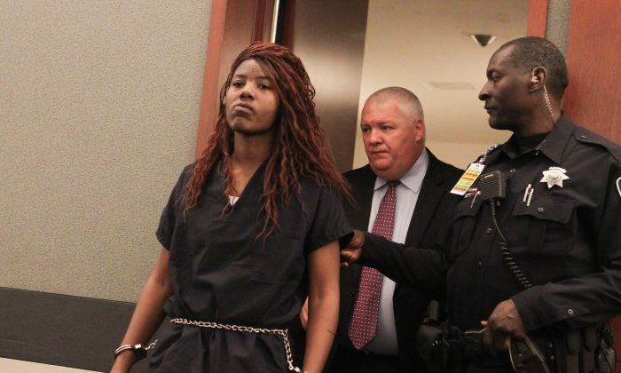 Lakeisha Nicole Holloway enters district court with one of her public defenders, Scott Coffee, for her arraignment Wednesday, Dec. 23, 2015, in Las Vegas. Holloway, who crashed her car into pedestrians on the Las Vegas Strip on Sunday, Dec. 20, has been charged with murder, child abuse and hit-and-run. (AP Photo/Chase Stevens)