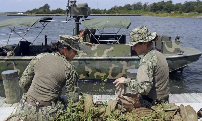 In this Aug. 13, 2013, photo, U.S. Navy Master-at-Arms Third Class Anna Schnatzmeyer, left, and Master-at-Arms Third Class Danielle Hinchliff, both of Coastal Riverine Squadron 2, eat their Meals Ready to Eat (MRE) as they participate in a U.S. Navy Riverine Crewman Course at the Center for Security Forces Learning Site at Camp Lejeune, N.C.  (AP Photo/Gerry Broome)
