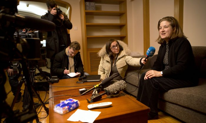 French journalist Ursula Gauthier (R) a reporter in China for the French news magazine L'Obs, speaks to the media in her apartment before leaving for the airport in Beijing on Dec. 31, 2015. (AP Photo/Mark Schiefelbein)