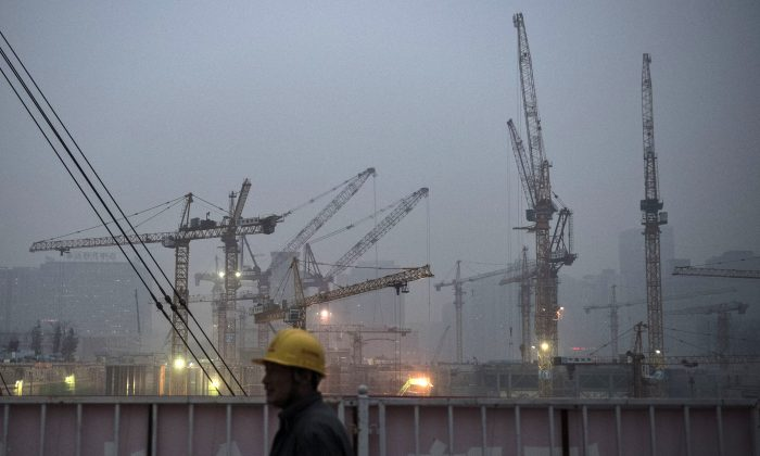 A Chinese laborer is backdropped by cranes at a construction site on December 9, 2014 in Beijing, China. (Kevin Frayer/Getty Images)